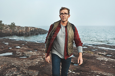 Buy stock photo Shot of a confident middle aged man walking on rocks next to the ocean while wearing a backpack outside during the day