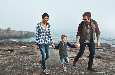 Buy stock photo Shot of a cheerful young family holding hands and walking together next to the ocean outside during the day