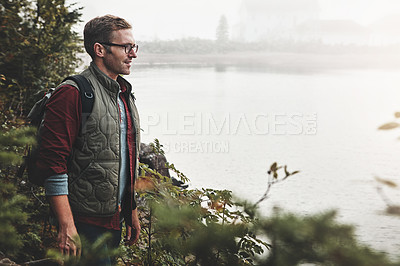 Buy stock photo Shot of an adventurous male backpacker out for a hike in nature