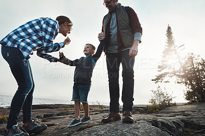 Buy stock photo Shot of a cheerful young family holding hands while taking a quick break from walking outside during the day