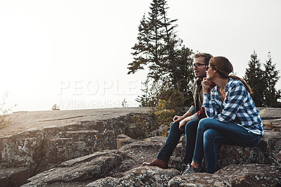 Buy stock photo Shot of a loving couple taking a break while out exploring nature