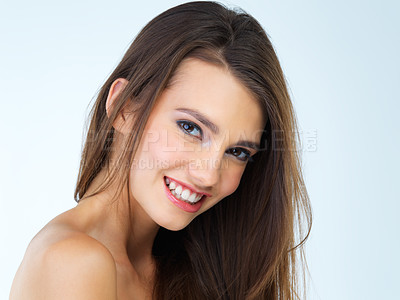 Buy stock photo Studio portrait of a beautiful young woman posing against a blue background