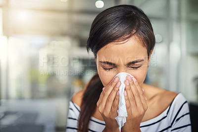 Buy stock photo Cropped shot of a young businesswoman blowing her nose with a tissue in the office