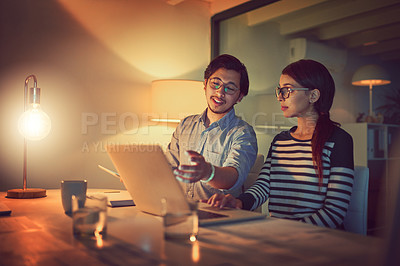 Buy stock photo Shot of two young designers working late on a laptop in an office