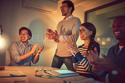 Buy stock photo Shot of a group of designers applauding while working late in an office