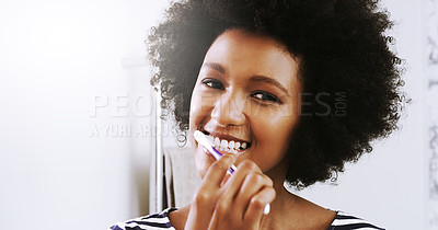 Buy stock photo Portrait of a cheerful young woman brushing her teeth while looking at her reflexion in the mirror in the bathroom at home