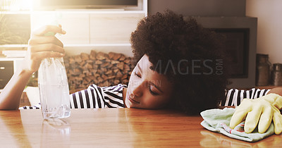 Buy stock photo Shot of a tired young woman resting her head on a table after trying to clean it with cleaning equipment at home during the day