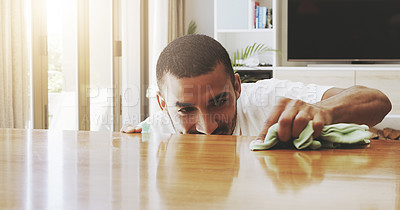 Buy stock photo Shot of a focused young man cleaning the surface of a table with cleaning equipment at home during the day
