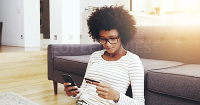 Buy stock photo Shot of a focused young woman seated on the floor while doing online shopping on her computer in the living room at home