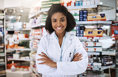 Buy stock photo Cropped portrait of an attractive young female pharmacist standing with her arms folded in a pharmacy