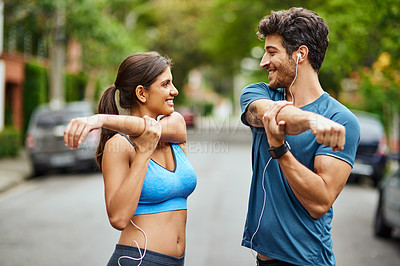 Buy stock photo Shot of a sporty young couple stretching while exercising together outdoors