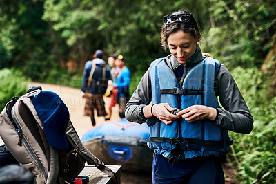 Buy stock photo Shot of a cheerful young woman putting on a life jacket to go river rafting outside during the day