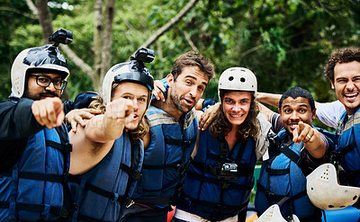 Buy stock photo Portrait of a group of cheerful young men wearing protective gear and standing arm in arm ready to go river rafting outside during the day