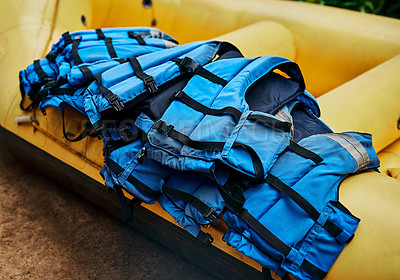 Buy stock photo Shot of a pile of river rafting life jackets lying on top of a rubber river rafting boat outside during the day