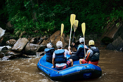 Buy stock photo Rearview shot of a group of unrecognizable people sitting in a rubber boat on a river while raising their paddles in the air outside during the day