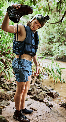 Buy stock photo Shot of a carefree young man holding his one shoe upside down to let water escape from it while standing next to a river