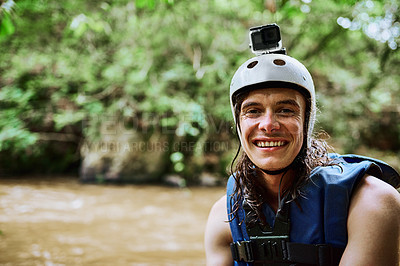 Buy stock photo Portrait of a cheerful young man wearing protective gear and a life jacket while standing next to a river outside during the day