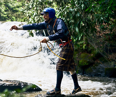 Buy stock photo Shot of a focused middle aged man wearing protective gear while throwing out a rope to somebody in a river outside during the day