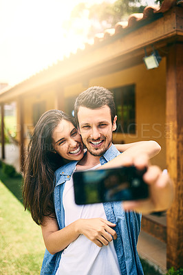 Buy stock photo Cropped shot of an affectionate young couple taking selfies outside with their house in the background