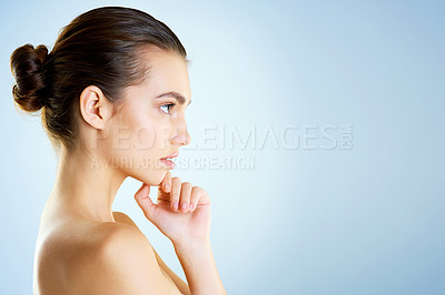 Buy stock photo Studio shot of a beautiful young woman looking thoughtful against a blue background