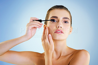 Buy stock photo Studio portrait of a beautiful young woman applying mascara against a blue background