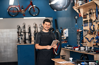 Buy stock photo Shot of a man using a digital tablet in a bicycle repair shop