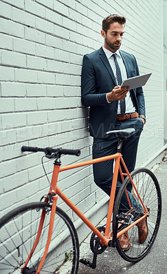 Buy stock photo Shot of a handsome young businessman using a digital tablet while standing alongside his bike outdoors