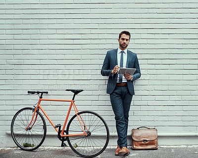 Buy stock photo Portrait of a handsome young businessman using a digital tablet while standing alongside his bike outdoors