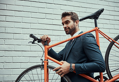 Buy stock photo Shot of a handsome young businessman carrying his bike on his shoulder outdoors