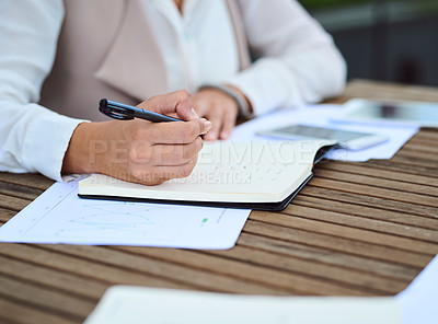 Buy stock photo Cropped shot of an unrecognizable young businesswoman taking notes while sitting in her office