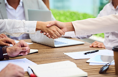 Buy stock photo Closeup shot of two unrecognizable businesspeople shaking hands during a meeting in the boardroom