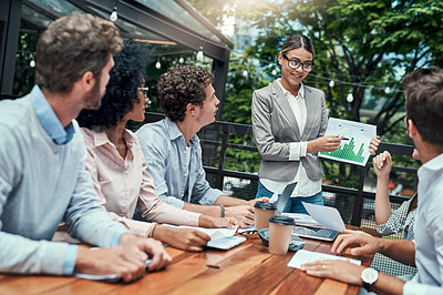Buy stock photo Shot of a group of colleagues having a meeting at a cafe