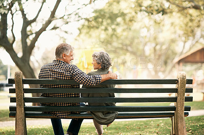 Buy stock photo Rearview shot of a happy senior couple relaxing on a park bench