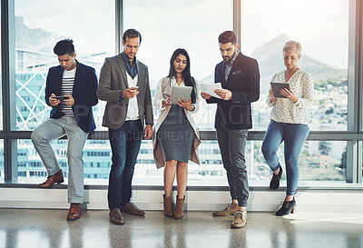 Buy stock photo Shot of a diverse group of businesspeople using wireless technology in an office