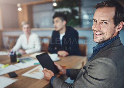 Buy stock photo Portrait of a mature businessman using a digital tablet while in a meeting in an office