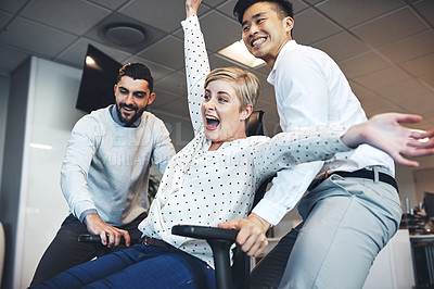 Buy stock photo Shot of businesspeople having fun by pushing taking their colleague for a ride in her chair in the office