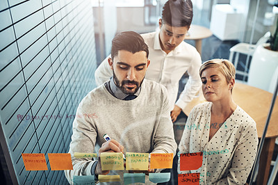 Buy stock photo Shot of businesspeople brainstorming with sticky notes on a glass wall in the office