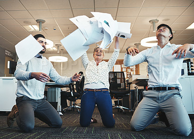 Buy stock photo Shot of businesspeople throwing paperwork in the air in the office
