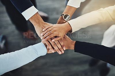 Buy stock photo High angle shot of a group of unrecognizable businesspeople joining their hands together in a huddle
