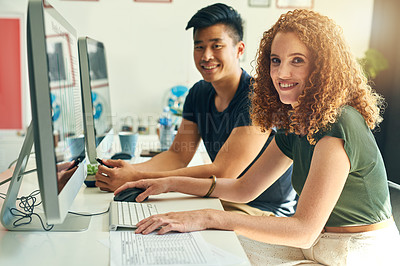 Buy stock photo Cropped portrait of two young creative businesspeople working on a computer in their office