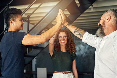 Buy stock photo Cropped shot of three creative businesspeople high fiving in their office