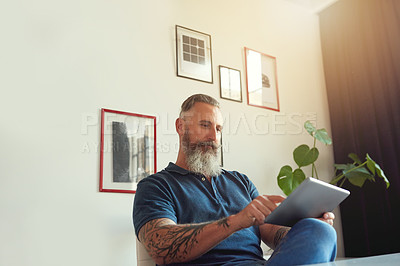 Buy stock photo Cropped shot of a handsome mature male designer working on a tablet in his office