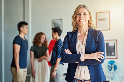 Buy stock photo Portrait of a creative employee while her colleagues are in the background in a modern office
