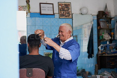 Buy stock photo Shot of a senior man trimming a client's hair in his barber shop