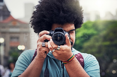 Buy stock photo Shot of a young man taking pictures with a camera in the city
