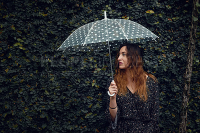 Buy stock photo Cropped shot of a beautiful young woman holding an umbrella outside