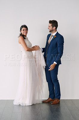 Buy stock photo Studio portrait of a newly married young couple standing against a gray background