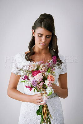 Buy stock photo Studio shot of a young bride holding a bunch of flowers against a gray background