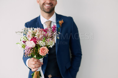 Buy stock photo Studio shot of a handsome young groom holding a bunch of flowers a gray background
