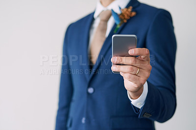 Buy stock photo Cropped studio shot of a stylish groom using a mobile phone against a gray background